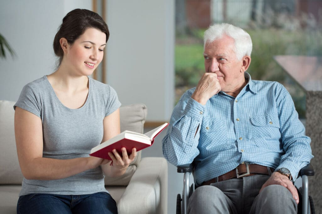 Senior-care-assistant-reading-book